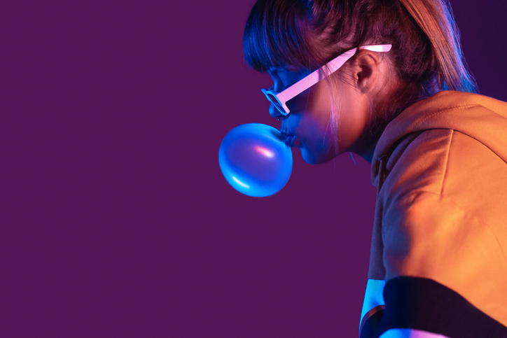 Teen igen girl wear stylish trendy sunglasses and hoodie blowing bubble gum profile side view, pretty young woman fashion cool model with bubblegum 80s at party purple studio background, copy space