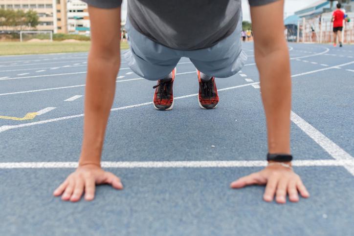 Sport man doing push ups exercise on the blue running track in stadium.