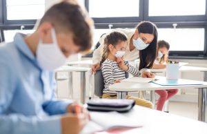 Group of children with face mask back at school after covid-19 quarantine and lockdown.