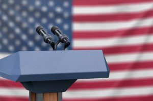 Flag of the United States at a press conference with microphones