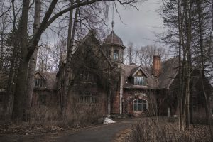 Old abandoned gothic house. The ruined mansion stands in the park. Gothic background. Halloween party place