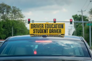 Student driver sign on top of car at stoplight