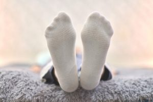 Woman resting on sofa in white striped socks, close up.