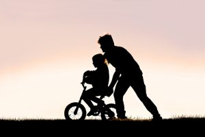 Father Helping his Young Child Learn to Ride Bike with Training Wheels