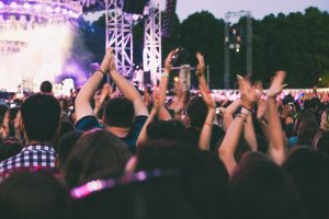 A big concert crowd having fun in front of the stage.