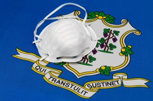 Connecticut state flag and N95 face mask. Concept of state and local government face covering mandate, order, requirement and social distancing during Covid-19 coronavirus pandemic