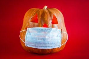 Halloween pumpkin in a protective medical mask on a red background