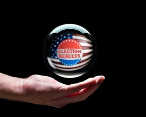 Hand holding a crystal glass forecasting ball to predict the result of the election