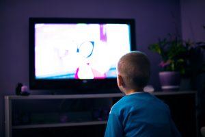 Boy watching television in dark