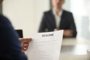 Job interview in office, focus on resume, close up view
