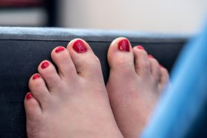 Female feet on a blue couch. Red nail polish, relaxing.
