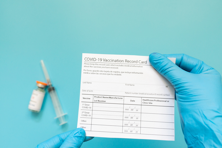 Doctor is holding a vaccination record card and corona virus vaccine vials. Passport of immunity to the coronavirus in the hands of a male doctor. Health passport.