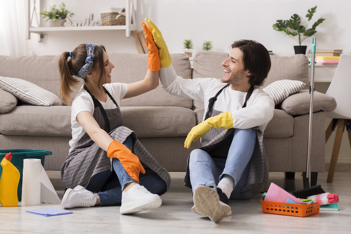 Happy Couple Giving High Five To Each Other After Cleaning Apartment