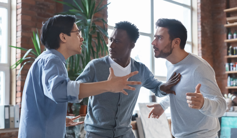 Multiracial coworkers having quarrel in office, conflict of interest