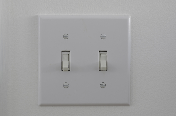 white Double house light switch platein OFF position on a white wall