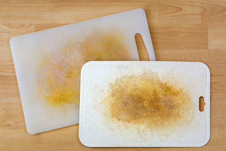Dirty white plastic cutting board with dark stains, scratch