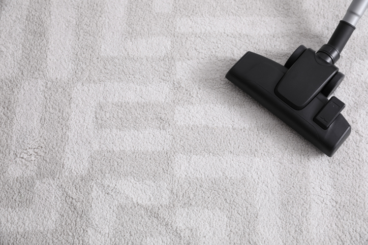 Modern vacuum cleaner on carpet indoors. Space for text