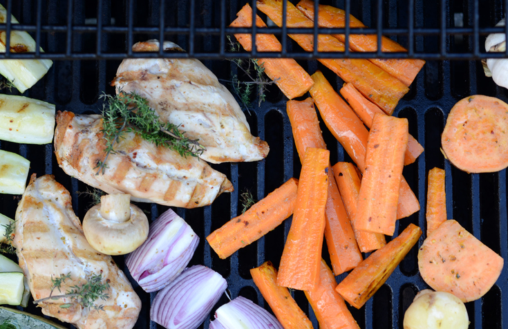 Chicken and vegetables cooking on an outdoor grill