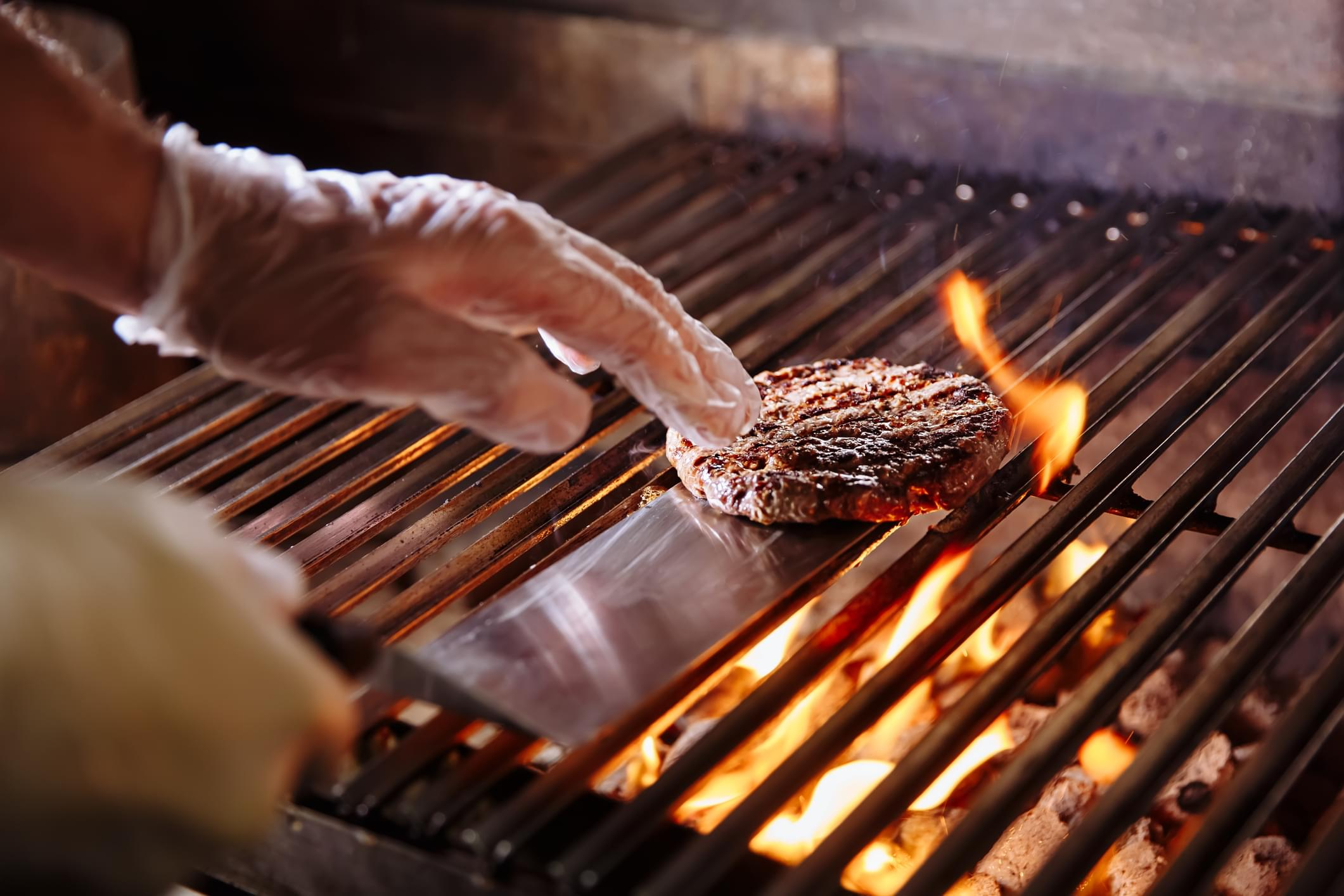 Chef making burger. Beef or pork meat barbecue burgers for hamburger prepared grilled on bbq fire flame grill. Close-up shot of chef's hands turn the chop on the grill