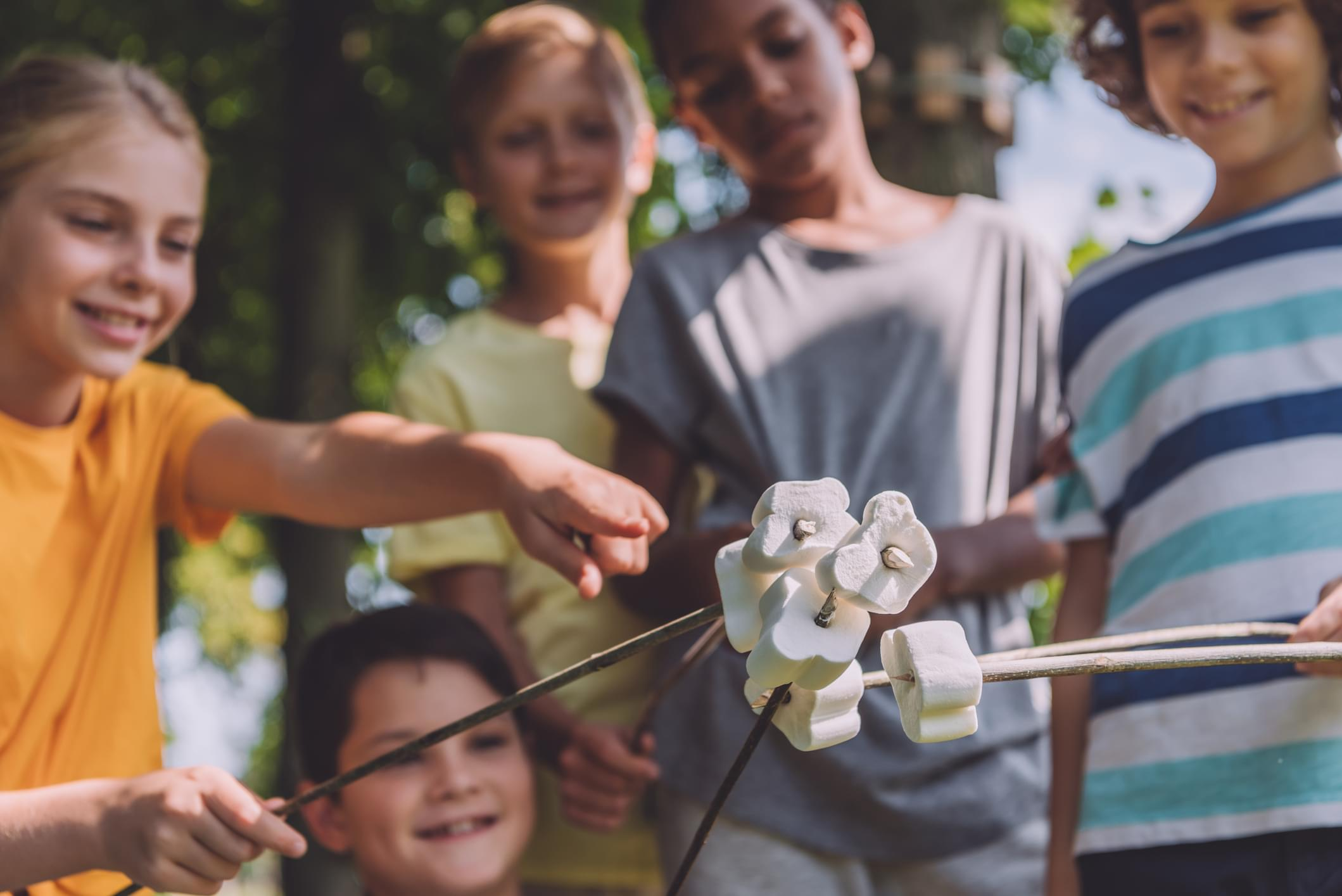 selective focus of kid pointing with finger at sweet marshmallows in sticks near multicultural boys