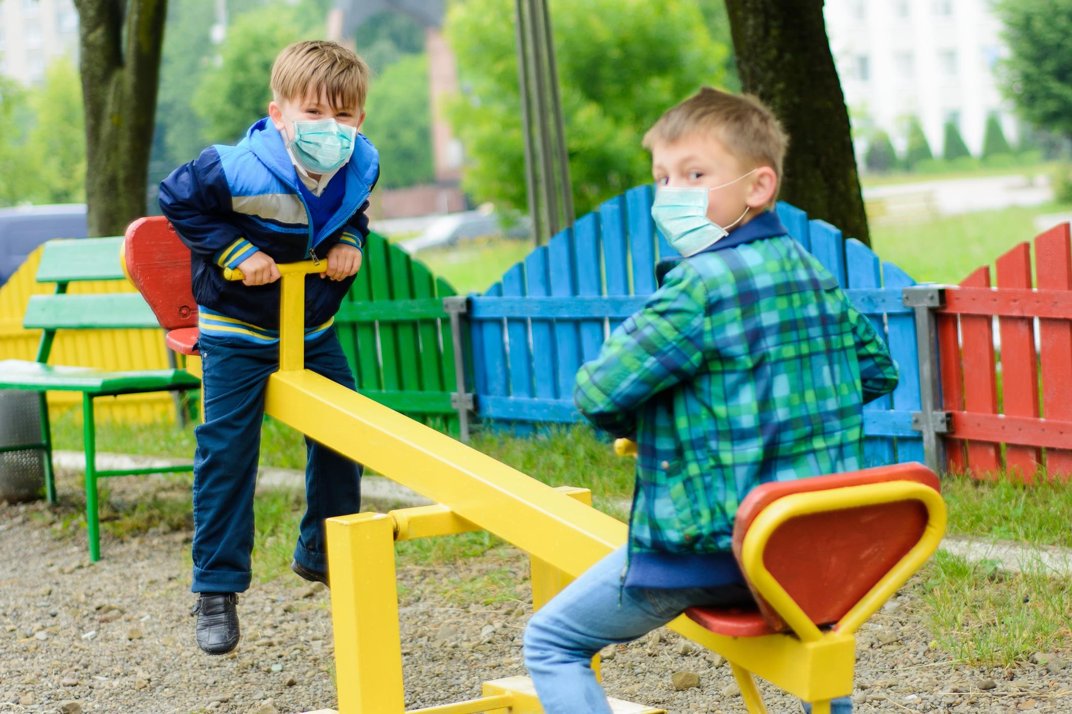 Children school in medical masks play at a quarantine playground during a coronavirus pandemic