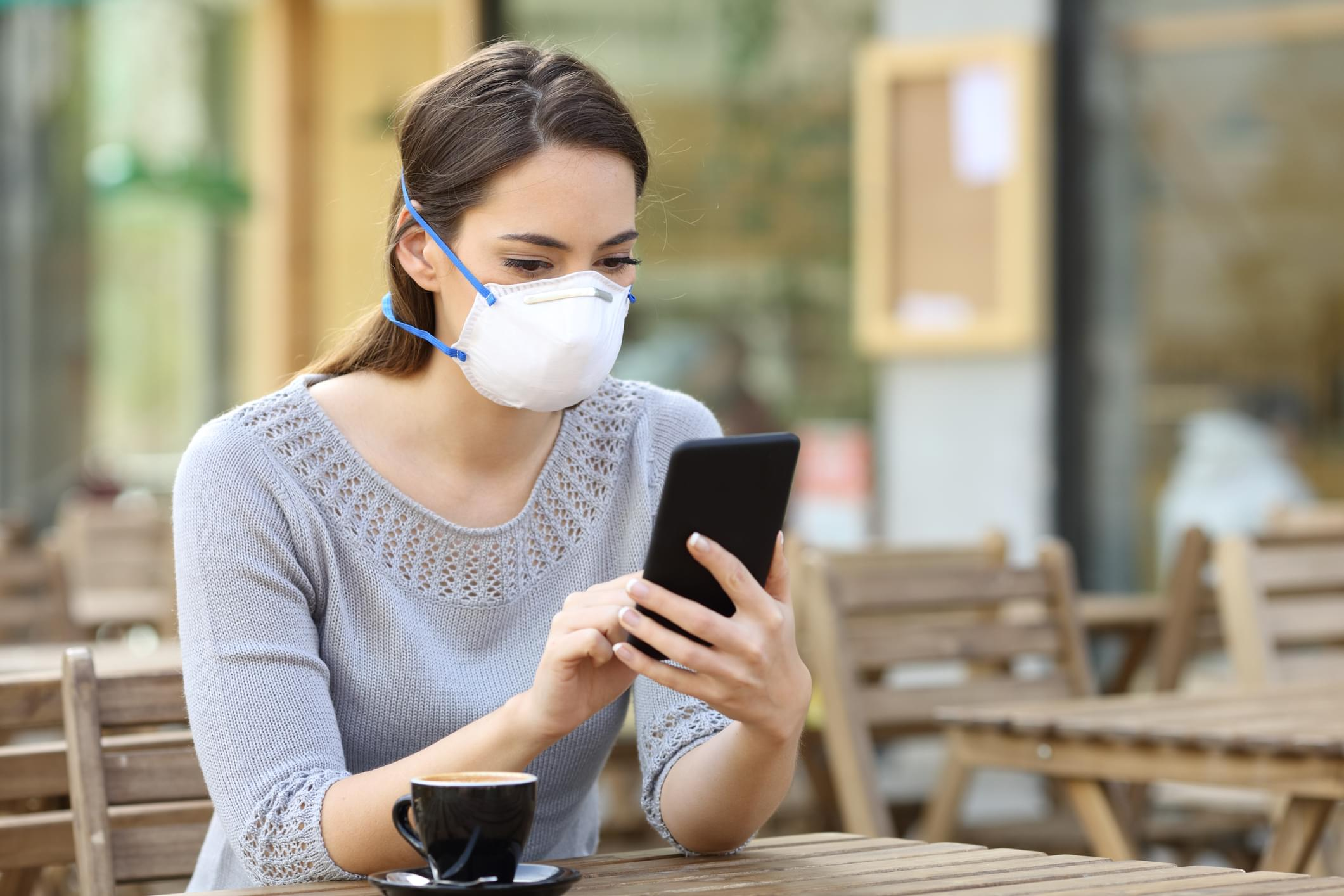 Woman with mask checking news on phone