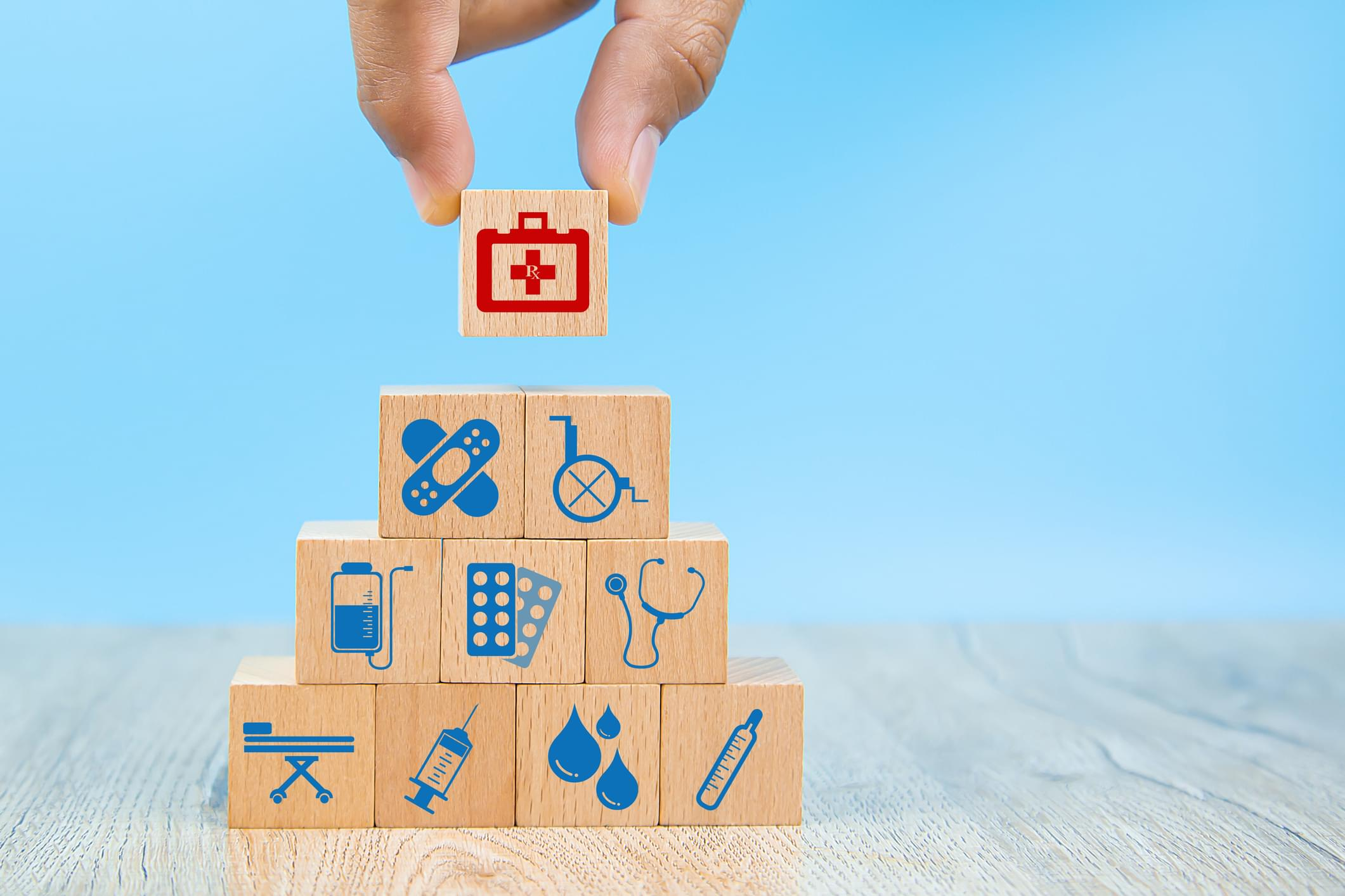 Close-up hand choose Health care and medical symbols on wooden blocks toy stacked in Pyramid shape for health insurance concepts.