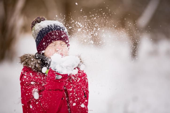 Portrait of cute kid boy blowing snow from his hands on a winter day. Child playing outdoors. Lifestyle concept