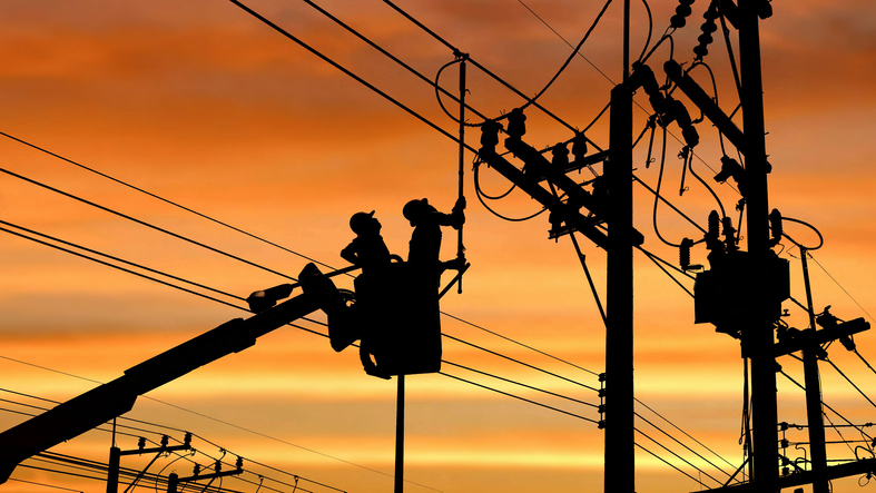 Silhouette two electricians with disconnect stick tool on crane truck are working to install electrical transmission on power pole