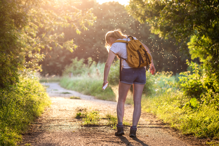 Woman with backpack applying insect repellent agains mosquito and tick outdoors