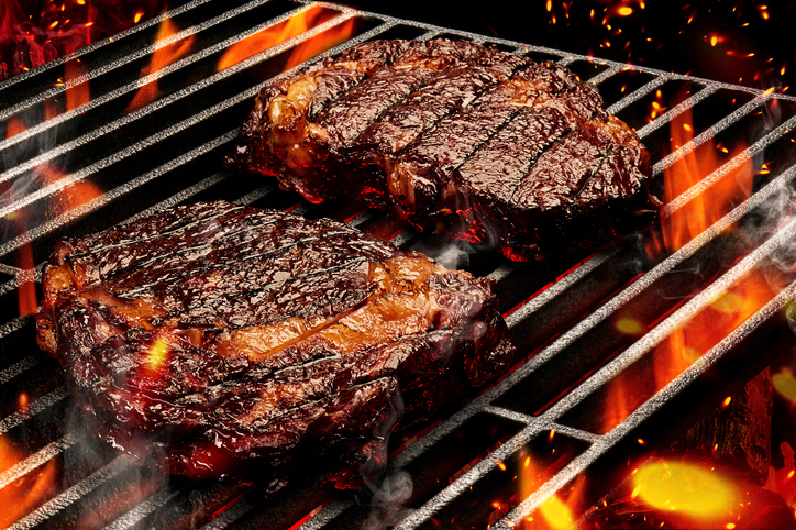 Process of preparing two pork or beef steaks. Meat roasted on metal portable barbecue BBQ grill with bright flaming fire and ember charcoal. Close up