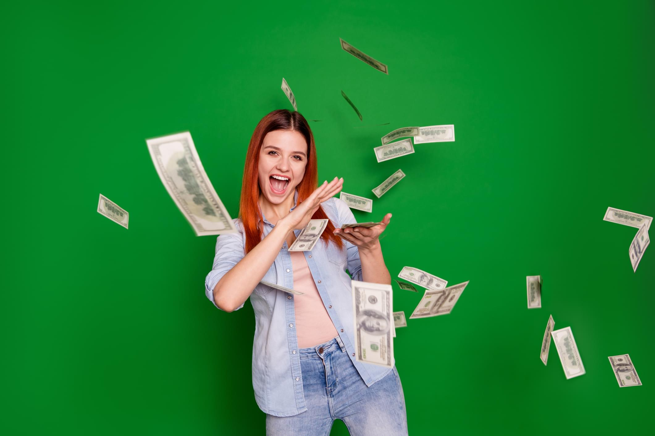 Portrait delighted ecstatic lady hold hand get salary wages rich aim positive cheerful satisfied content beautiful trendy stylish wear jeans long straight hairstyle isolated on green background