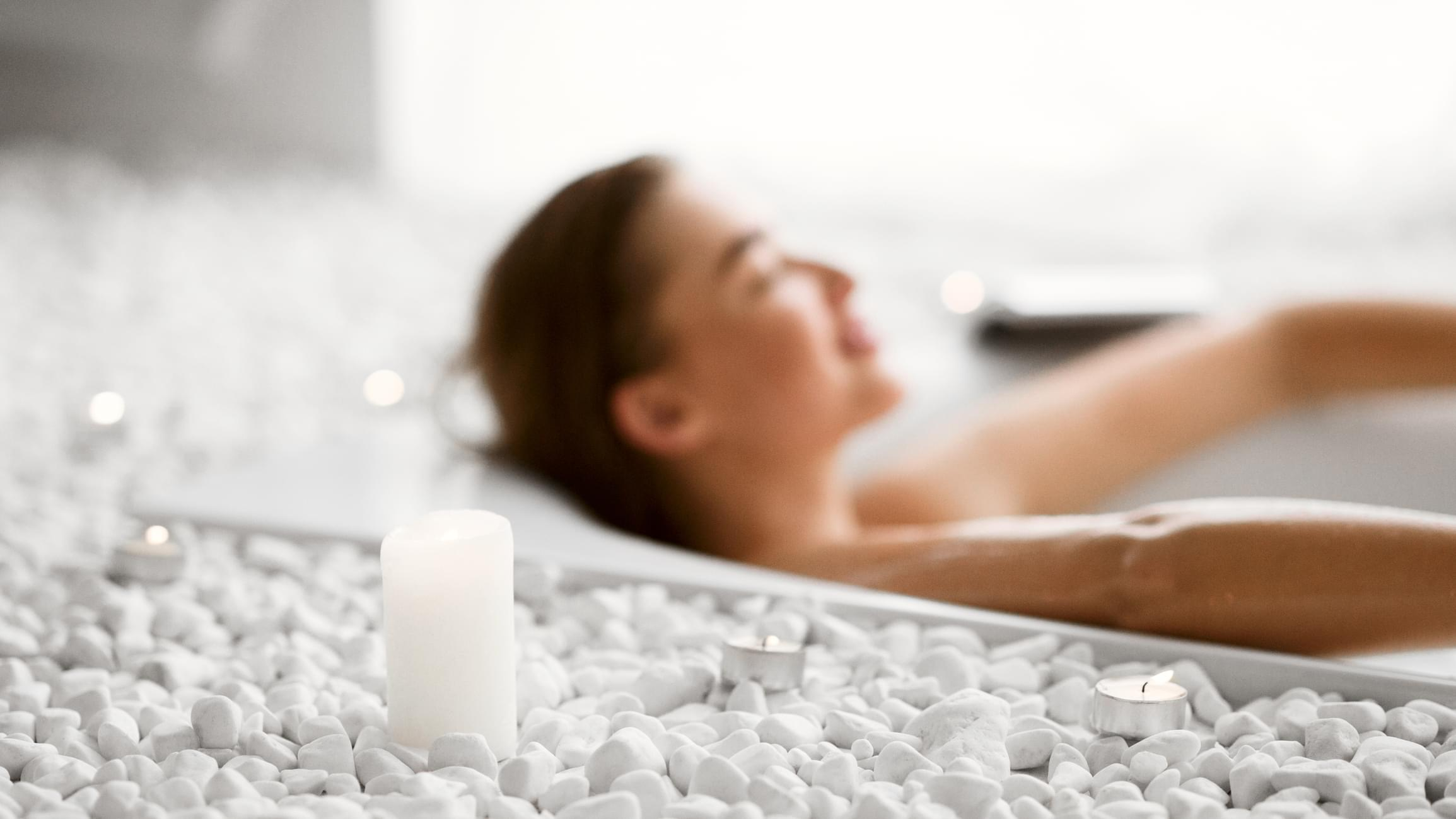 Young Woman Relaxing In Bath With Candles