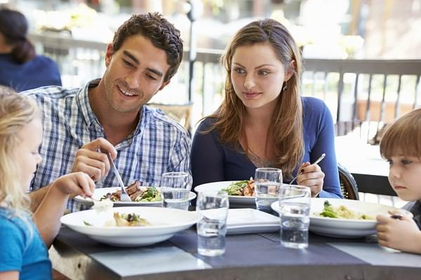Family Enjoying Meal At Outdoor Restaurant