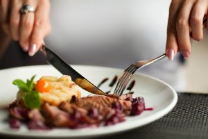 Female hands with a dinner at restaurant.