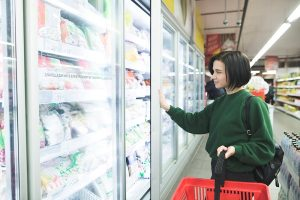 The buyer near the refrigerator in the supermarket. A beautiful girl buys food at a supermarket. The buyer selects the goods in the store