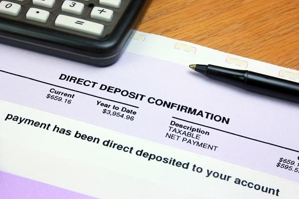 direct deposit summary on a table with a pen and calculator