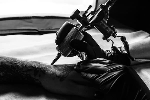 Close up picture of tattooist make a tattoo on clients arm in bw. Master works on the desk in black sterile gloves and hold a tattoo machine.