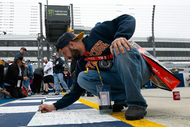 DOVER, DE - MAY 06:   A fan signs the finish line during pre-race ceremonies the Monster Energy NASCAR Cup Series AAA 400 Drive for Autism at Dover International Speedway on May 6, 2018 in Dover, Delaware.  (Photo courtesy of NASCARmedia.com/by Robert Laberge/Getty Images)