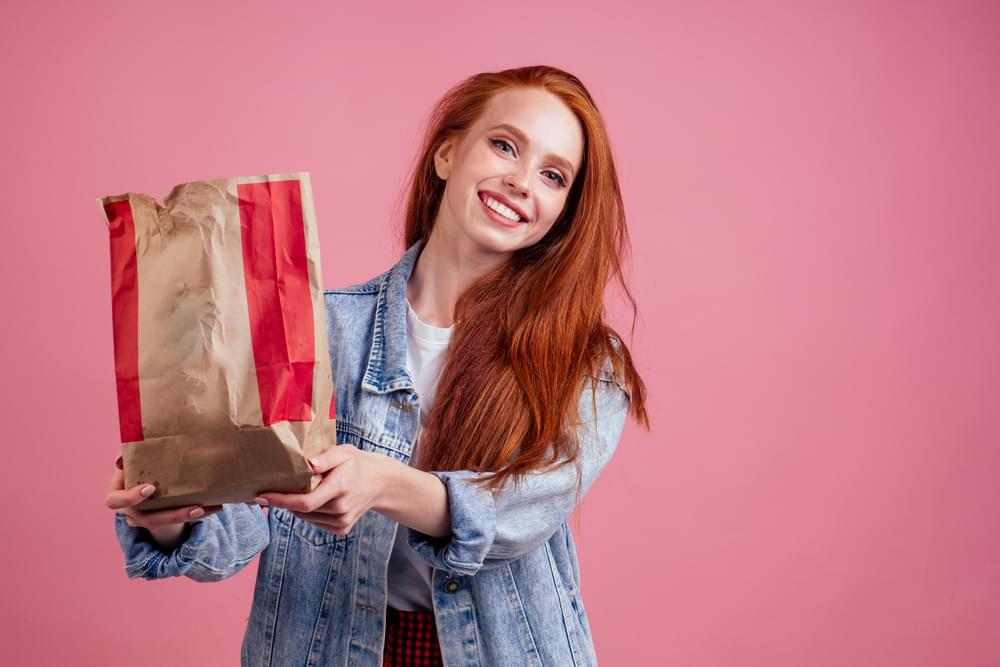 happy long red-haired ginger woman holding paper eco bag package with chips in studio pink background