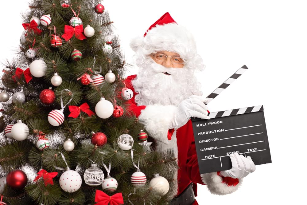 Santa Claus holding a movie clapperboard