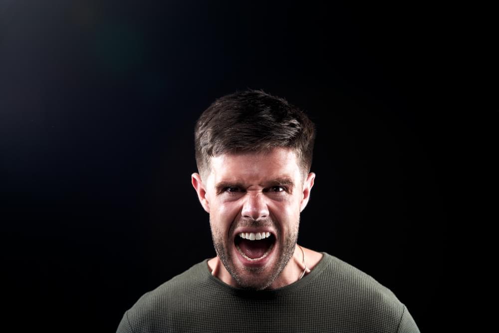 Head And Shoulders Studio Shot Of Angry Man Shouting At Camera