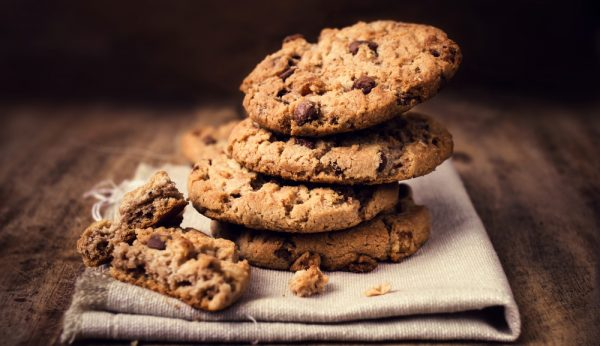 Chocolate cookies on white linen napkin on wooden table. Chocolate chip cookies shot on coffee colored cloth,