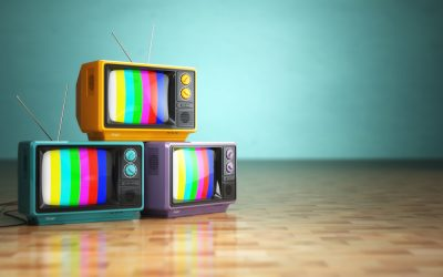 Vintage television concept. Stack of retro tv set on green backg