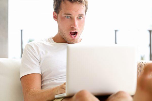 Shocked surprised man looking at laptop computer