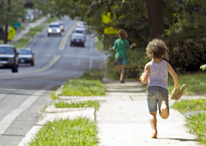 FILE - In this June 12, 2015 photo, Dvora Meitiv, rear, runs home with her brother Rafi after their mother Danielle Meitiv met them at the school bus stop in Silver Spring Md. Danielle Meitiv and her husband Alexander were cleared in two child-neglect cases after Maryland authorities had charged them with neglect for previously allowing their children to walk home alone from neighborhood parks. Rhode Island lawmakers are weighing legislation in 2016 that would punish parents for leaving a child under 7 years old alone in a car, ban kids under 10 from being home alone, and bar preschoolers from going outside for recess in freezing weather. (AP Photo/Jose Luis Magana, File)