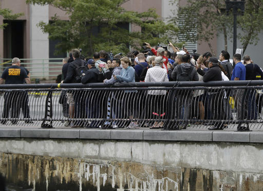 Onlookers gather near the Hoboken Terminal following a train crash, Thursday, Sept. 29, 2016, in Hoboken, N.J. A commuter train crashed into the rail station during the morning rush hour, causing serious damage. (AP Photo/Julio Cortez)