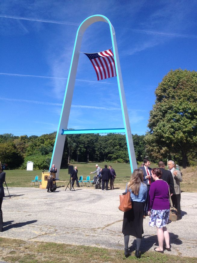 Visitors view the repainted arch at Rocky Point during its unveiling. Photo by Steve Klamkin WPRO News